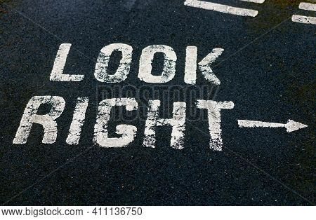A Look Right Sign Painted In White Paint Onto The Black Tarmac Of A Road And Pathway
