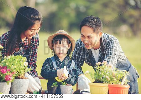 Family Child Girl Helping Parent Care Plant Flower In Garden. Young People Mother, Father And Daught