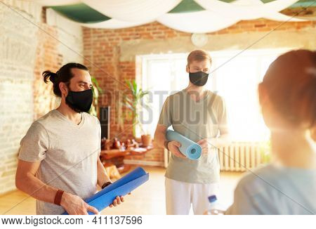 fitness, sport and healthy lifestyle concept - group of people wearing face protective black masks for protection from virus disease with mats at yoga studio or gym