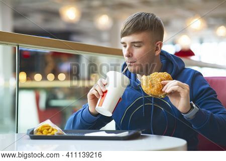 Young Guy Eats On A Food Court, Fast Food. The Man Eats A Burger And Drinks Soda Water. Bad Food, St