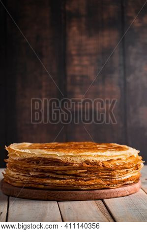 A Stack Of Thin Pancakes On A Dark Wooden Background. A Traditional Dish Of Crepes For The Holiday M