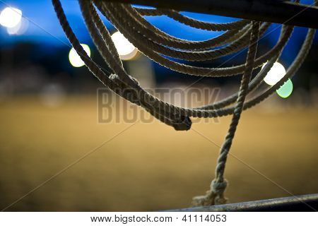 Cowboy's rope hanging on fence between events at a Texas rodeo, at sunset poster