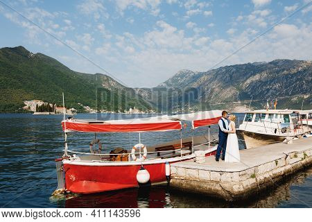 The Bride And Groom Are Embracing On The Pier In The Bay Of Kotor, Tourist Boats Near The Pier