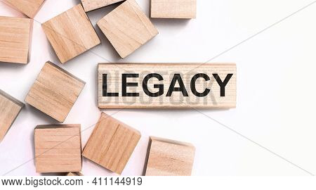 On A Light Background, Wooden Cubes And A Wooden Block With The Text Legacy. View From Above