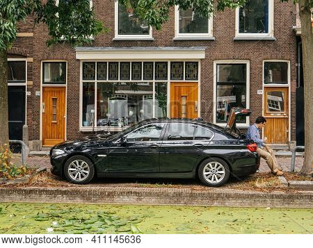 The Netherlands - Aug 19, 2018: Pensive Businessman Drinking From A Cup Coffee Or Thea Sitting On Th