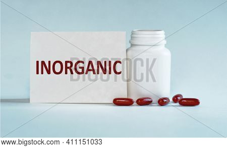 On A Light Blue Background A Card With The Text Inorganic Near The White Bottle Pills.