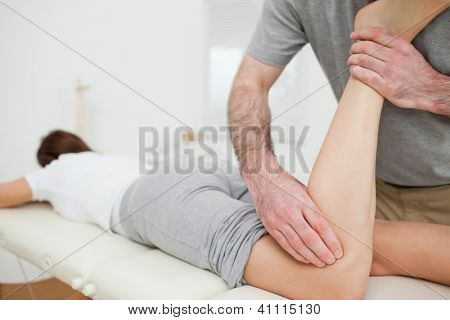 Woman lying while being massaged by a man in a room