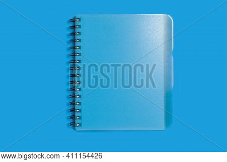 Closed Spiral Notebook Lying On A Blue Background. Concept Of Office Stationary. Free Copyspace