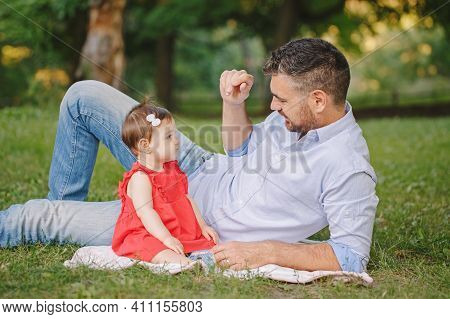 Middle Age Caucasian Proud Father Playing With Baby Daughter. Family Dad And Daughter Sitting Togeth