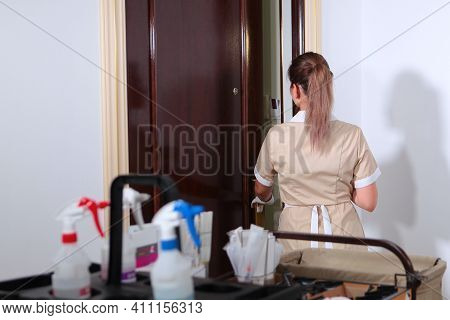 A Uniformed Maid Opens The Door Of A Hotel Room. Cleaning And Disinfection Of Rooms. A Maid With A T