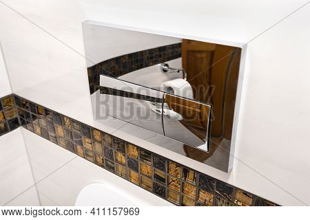 A Chrome Plated Toilet Flush With Two Buttons Placed In The Wall Of A Bathroom Covered With Ceramic