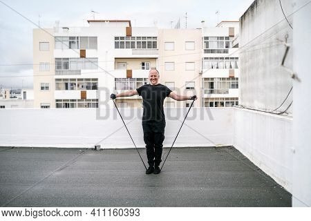 A Man Exercising With Gum On The Rooftop During Lockdown