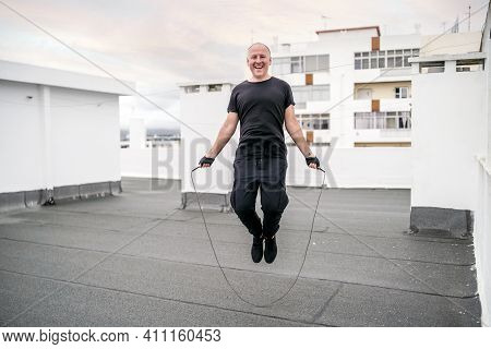 A Man Exercising On The Rooftop Using Jumping Rope During The Lockdown