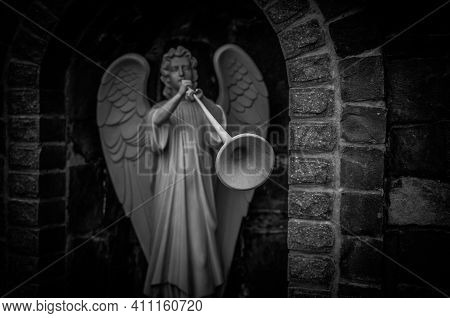 Landscape In Black And White With A Statue Of An Archangel Blowing A Trumpet Near The Village Church