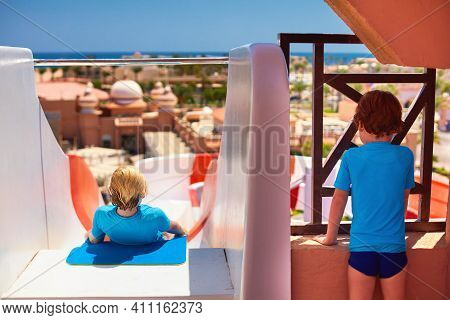 Happy Kids Are Having Fun, Sliding The Water Slide In Aqua Park During Summer Holidays