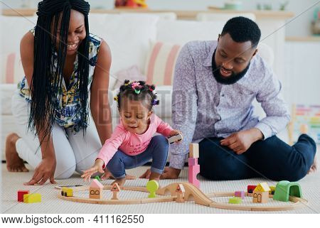 Happy Family With Toddler Baby Playing Toy Railway Together At Home