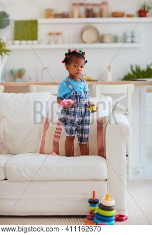 Cute African American Baby Girl Playing Toys, Standing On Sofa At The Cozy Living Room