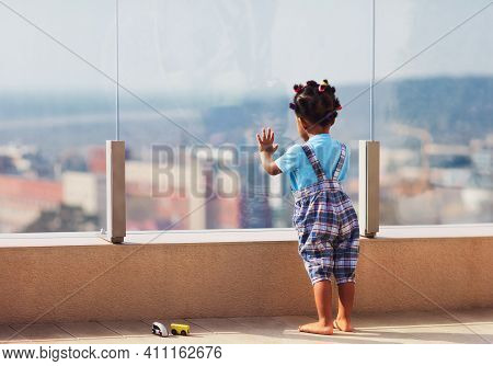 Cute Toddler Baby Watching The Cityscape From The Rooftop Patio With Glass Balustrade