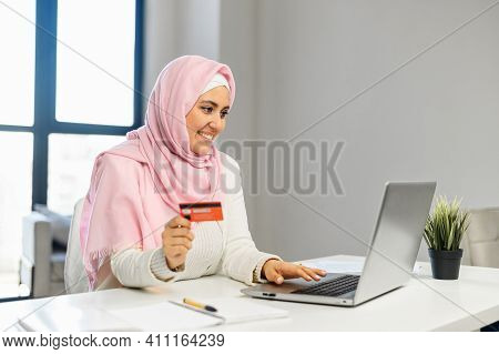 Happy Young Muslim Woman Wearing Hijab And Smart Casual Wear Holds A Debit Card And Making Online Or