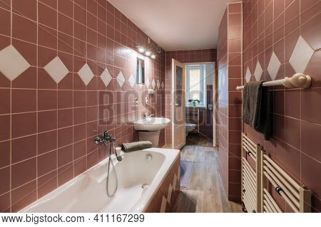 Old Bathroom Of A Family House With Bath And Shower, Wash Basin And Mirror With Lamp. The Walls Are