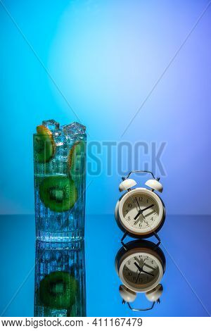 A Glass Of Water With Ice And Slices Of Kiwi Standing On A Mirror Table Next To The Alarm Clock. Bod