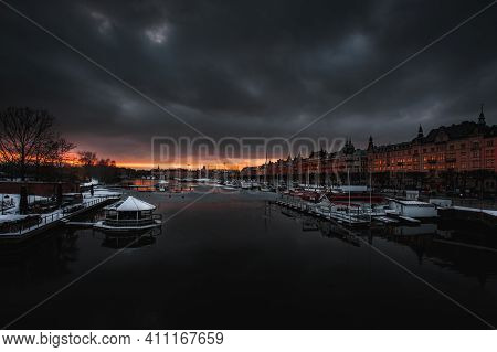 Red Sunset With Dark Clouds Over The Pier Of The Winter City (stockholm). The Waterfront Is Lined Wi