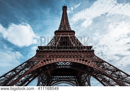 Ultra Wide Angle Of Eiffel Tower Over Blue Sky With White Clouds And Bright Glow Of Sun In Paris, Fr