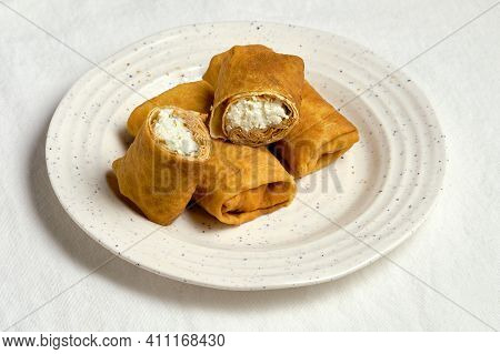 Fresh Baked French Crepes Or Russians Blinis Stuffed With Fresh Sweet Cottage Cheese. White Plate On