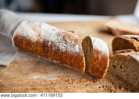 Freshly Cut Crusty Baguette On A Wooden Cutting Board. Sliced Traditional French Bread. Close-up Wit