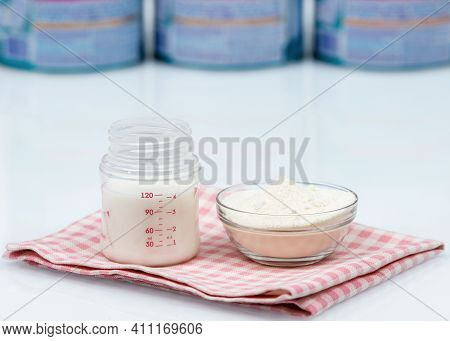 Artificial Feeding Of Children. Bottle For The Mixture And Infant Formula Powdered Milk On White Tab