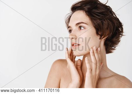 Skincare Concept. Beautiful Young Woman Standing In Profile, Touching Pure Hydrated Skin, Looking Le