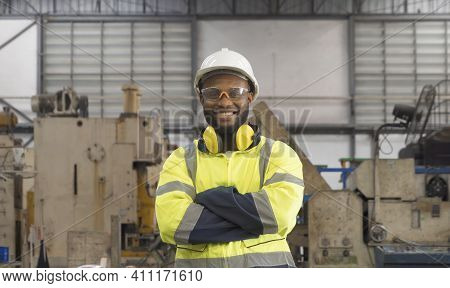 Smiling Black African American Man, An Engineer Or Worker Working In Manufacturing Factory With Equi