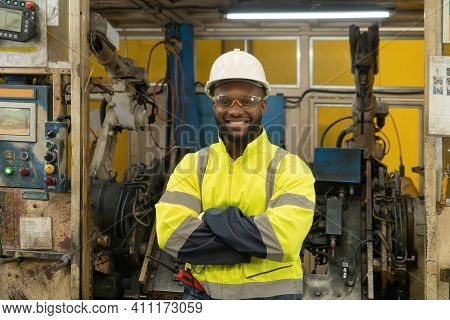 Smiling Black African American Man, An Engineer Or Worker With The Smart Robot Welding Hand System A