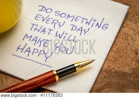 Do something every day that will make you happy - inspirational handwriting on a napkin, happiness and personal development concept