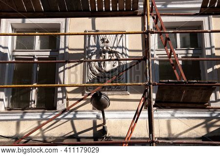 Rusty Metal Scaffolding In Front Of Historic Building Wall With Ornate Sculptural Relievo Details An