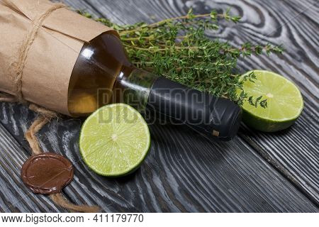 Alcohol Bottle. Wrapped In Paper. Nearby Thyme And Lime Halves. On Pine Boards.
