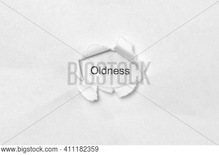 Word Oldness On White Isolated Background, The Inscription Through The Wound Hole In Paper. Concept
