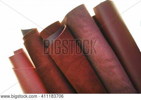 Genuine Leather Isolated On White Background.red And Burgundy Genuine Leather In Rolls Close-up On A