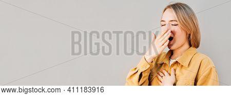 Beautiful Woman Yawns Of Boredom On Gray Background