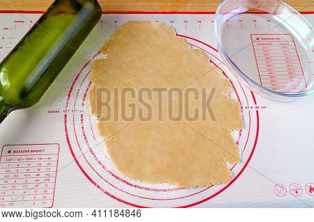 Dough After Rolling On A Baking Mat With Glass Baking Plate And Wine Bottle Used As A Rolling Pin