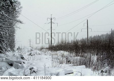 Wooden Pole Power Line On Winter Blue Sky Backgound And Forest. Stock Photo With Empty Space For Tex