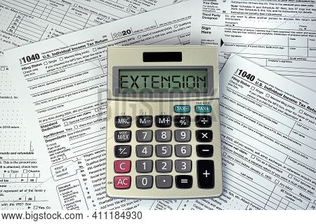 Extension Text On Business Calculator Screen With 2020 1040 Internal Revenue Tax Forms