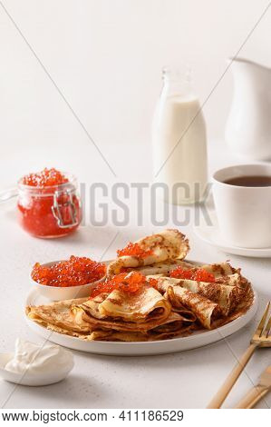 Russian Thin Pancakes Or Blini With Red Caviar On White. Shrovetide. Close Up. Vertical Format.