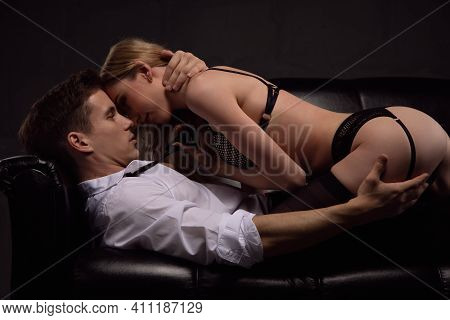 Young Attractive Sexy Couple Kissing In A Passionate Embrace Lying On A Black Leather Sofa