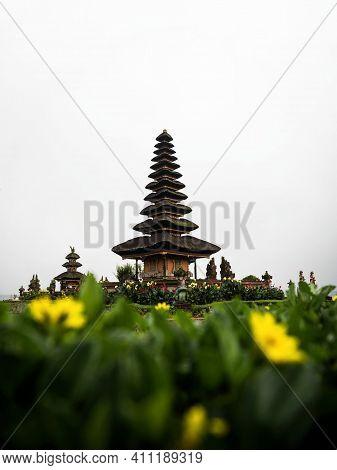 Yellow Flower Green Plant Frame Of Pura Ulun Danu Beratan Hindu Shiva Water Temple In Bedugul Lake B
