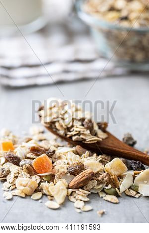 Beakfast cereals in wooden scoop. Healthy muesli with oat flakes, nuts and raisins