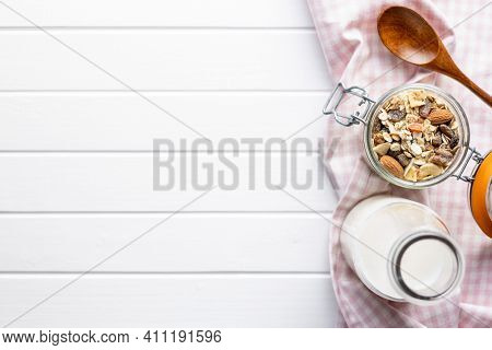Beakfast cereals in bowl and milk in bottle. Healthy muesli with oat flakes, nuts and raisins. Top view.