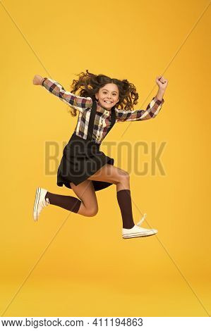 Energy And Ambition. Energetic Girl Run To School. Happy Child In Midair Yellow Background. Childhoo