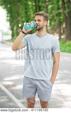 Long Workout Is Over. Man With Athletic Appearance Holds Bottle With Water. Athlete Drink Water Afte