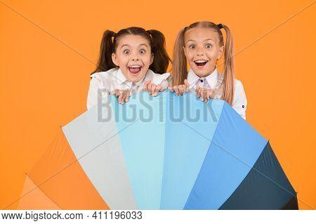 Umbrella Surprise. Surprised Girls Hiding Behind Umbrela On Yellow Background. Little Children Looki